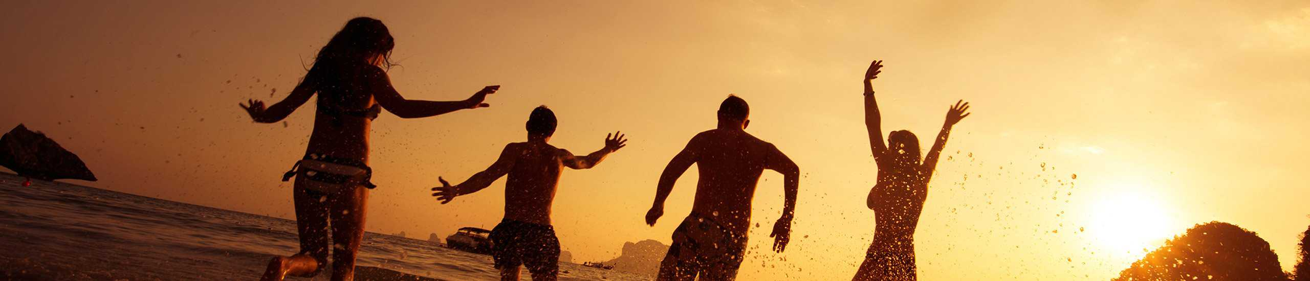People jumping in water at the beach at sunset